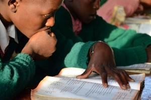 Ein Junge liest in einem Schulbuch (Foto: Emmy Chirchir)