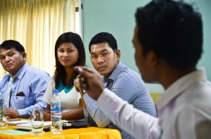 Ou Ratanak looks on as a student makes a point during a mock debate held to encourage critical thinking on gender issues among Cambodian youth
