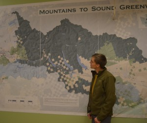 Ben Hughey stands next to the biggest map he's ever made - a two-meter-tall, five-meter-wide map of the Mountains to Sound Greenway (Photo: E. O'Neill)