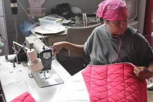 Alisha works on a coat blanket