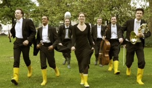 Musicians in yellow rubber boots carrying instruments