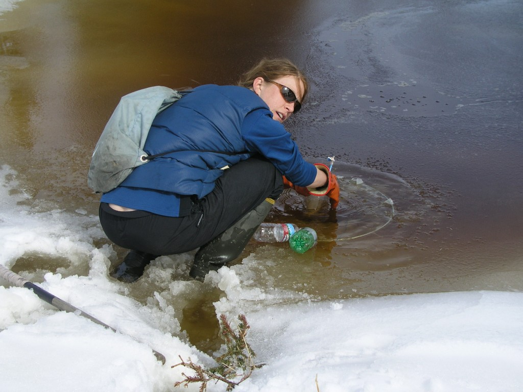 "Scientist Laura Brosius collects methane from Eight Mile Lake using an ""umbrella trap""."