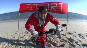 "Michael Wigge in front of a sign saying ""START"" in the northernmost tip of Germany, the so-called ""Ellbow"" on the island of Sylt"