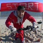 """Michael Wigge am Strand vor einem """"Start""""-Schild - am nördlichsten Punkt Deutschlands, dem Ellenbogen auf der Nordseeinsel Sylt"""