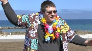 ein junger Mann mit Hawaiihemd und Kunstblüten-Kette tanzt Samba