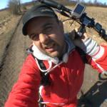 Michael Wigge trägt seinen Tretroller über einen schlammigen Feldweg