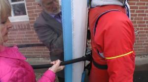Ein Mann und eine Frau befestigen eine Spezialjacke mit Segel an Michael Wigge