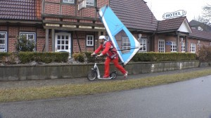 Michael Wigge auf seinem Tretroller mit Surfsegel auf dem Rücken