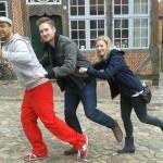 Michael Wigge, Steffen Thamm und Dietke Studemund in Tretroller-Pose vor einem Fachwerkhaus