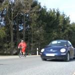Michael Wigge mit dem Tretroller unterwegs auf einer Landstraße, neben ihm fährt ein Auto