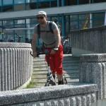 Michael Wigge fährt auf dem Tretroller durch eine Stadt