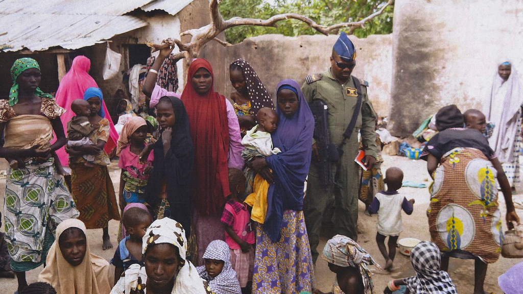 a member of the Nigerian Army standing with a group of women and children rescued in an operation against the militant Islamist group Boko Haram. © Picture-alliance/dpa