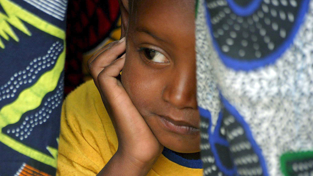 A young Senegalese girl under cover in her mother's traditional clothes, while they attend the official renouncement ceremony of Female Genital Cutting (FGC) in Kidira, eastern Senegal, Sunday 12 March 2006.  Rights: picture alliance/dpa