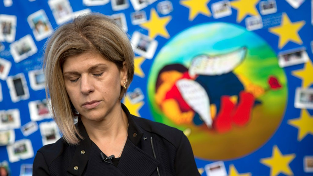 Fatima Kurdi, from Canada, stands next to a painting of her late nephew, Aylan Kurdi, on a board outside of EU headquarters on Monday, Sept. 14, 2015. Aylan Kurdi (3) and his family was on the way to her when the small rubber boat he and his family were in capsized in a desperate voyage from Turkey to Greece. © picture-alliance/AP Photo/V. Mayo