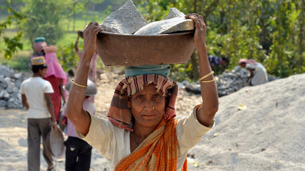 An Indian woman carries stones on her head at a rock processing area in Assam © Anuwar Hazarika/AFP/Getty Images