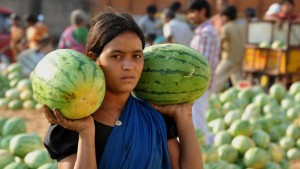 A female labourer carried away watermelons following an auction at the Gaddiannaram wholesale fruit market on the outskirts of Hyderabad. © NOAH SEELAM/AFP/Getty Images