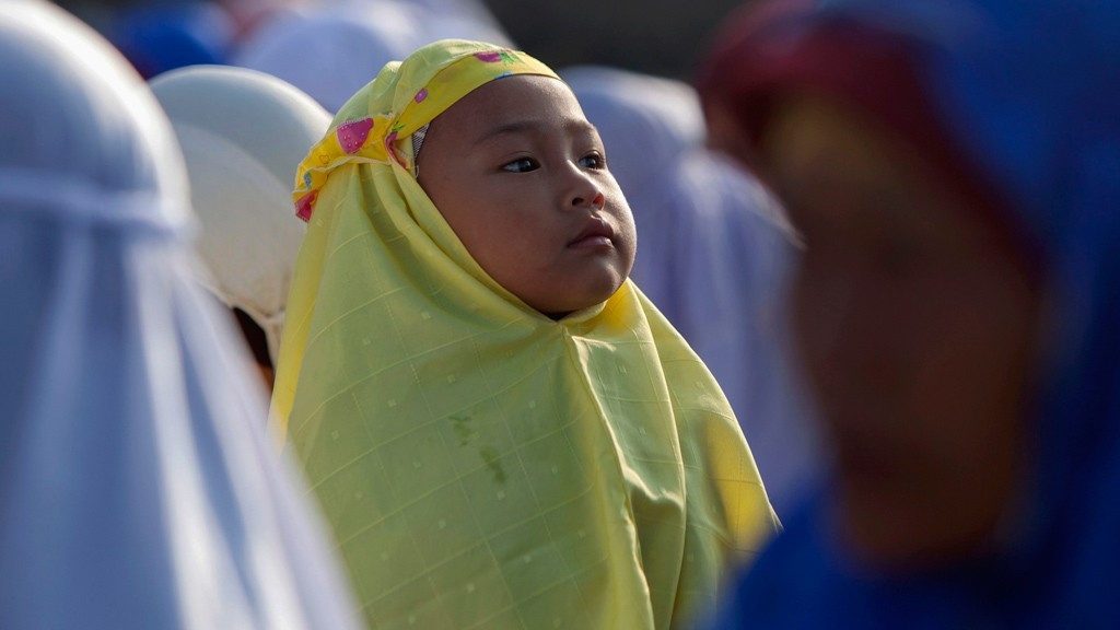A girl attends a mass prayer during Eid al-Adha festival in Kalitengah village, on the slopes of volcano Mount Merapi, Yogyakarta October 26, 2012. © Reuters