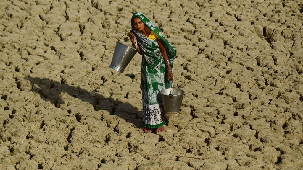 An indian woman walks on a dried and cracked water pond as she carries bucket to take drinking water. © Imago/Zuma Press