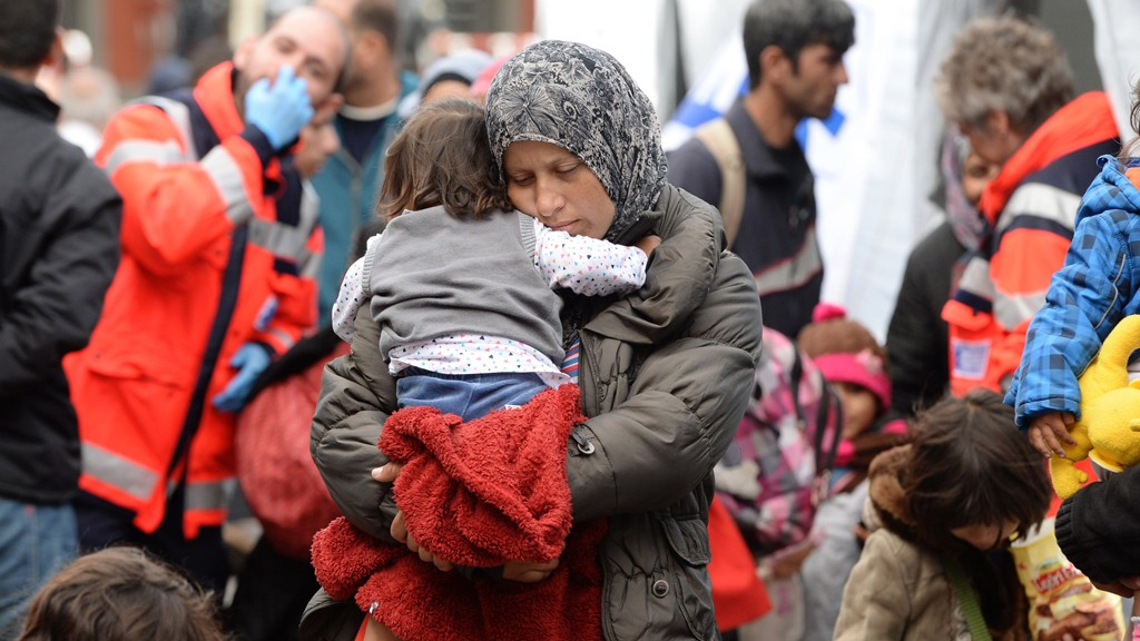 Migrant mother with a child waits for a first medical check after their arrival at the main railway station in Munich, southern Germany, on September 06, 2015.  @ Getty Images/AFP/C. Stache