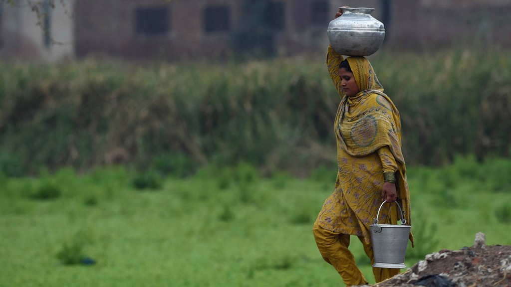 A Pakistani woman carries water pots make way for her home at a slum area © Arif Ali/AFP/Getty Images